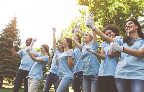 Group of happy volunteers celebrating success up in park