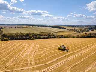 Countryside landscape aerial view from drone to agricultural field with combine on a blue sky background.