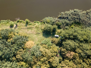Wall Mural - Aerial view from drone recreation place on a bank of river. Top view green trees, meadow and white car. Top view.