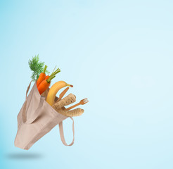 Fresh vegetables in bio eco cotton bags flying. Zero waste shopping concept. Plastic free.