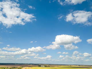 Cloudy aerial landscape with white clouds and fields on a blue sky background. Aerial view from drone.