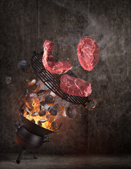 Kettle grill with hot briquettes, cast iron grate and tasty beef steaks flying in the air. Freeze motion barbecue concept.
