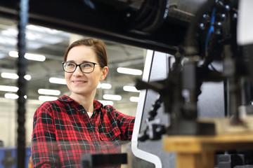 Fototapeta Drukarz. Uśmiechnięta kobieta, pracownik drukarni stoi w hali produkcyjnej na tle nowoczesnych maszyn drukarskich obraz