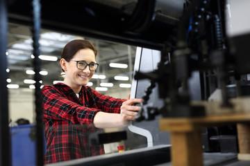 Fototapeta Drukarnia, introligatornia. Uśmiechnięta kobieta, pracownik drukarni stoi w hali produkcyjnej na tle nowoczesnych maszyn drukarskich obraz