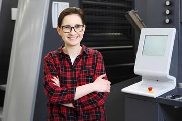Obraz Drukarnia. Praca w drukarni. Uśmiechnięta kobieta, pracownik drukarni obsługuje maszynę drukarską. - fototapety do salonu