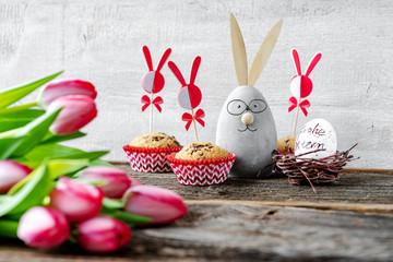 Lächelnder Dekohase zwischen Muffins und Tulpen wünscht Frohe Ostern