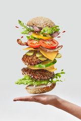 Deliciouse homemade burger on a woman hand with flying fresh ingredients on a white background. Copy space.