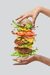 Girl's hands hold big tasty homemade burger with flying natutal ingredients on a white background. Copy space.