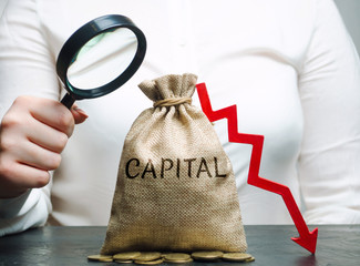 Woman analyzes data on the cost of capital in the company. Capital outflow. Unprofitable activity of the enterprise. Low capital ratio. Small income and deficit. Weighted average price indicator