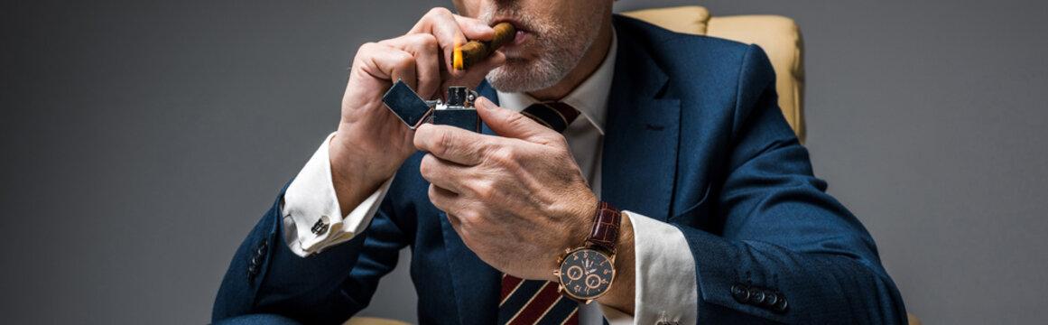 panoramic shot of mature businessman holding lighter while smoking cigar on grey