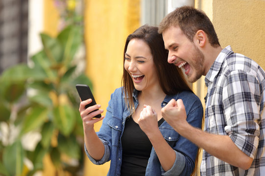 Excited couple finding online offers on phone in the street