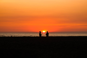 silhouette of two men talking at sunset time