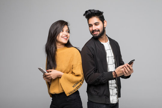 Beautiful young indian couple holding mobile phones and standing back to back against grey background