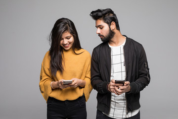 Curious indian boyfriend is spying his lovers smartphone standing isolated on gray background Wall mural