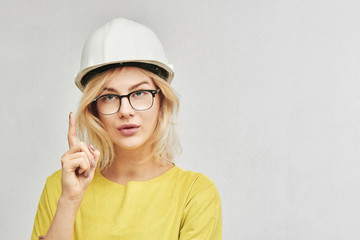 Young sexy blond woman engineer in construction helmet and glasses looks and shows index finger up isolated on white background