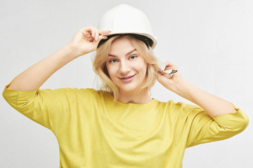 Portrait of young sexy blond woman engineer in construction helmet posing, gently smiling at camera isolated on white background in studio