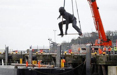 "Britain's largest bronze sculpture, ""Messenger"" arrives by barge in Plymouth Sound before being taken by road to the Theatre Royal in Plymouth"