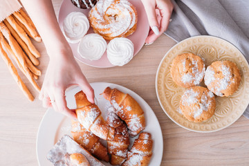 Homemade sweet bakery. Dessert assortment on table. Woman taking croissant from plate of fresh pastries.