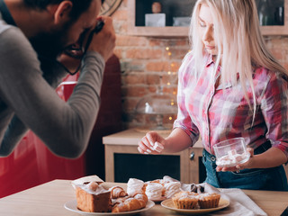 Cooking blog. Hobby and lifestyle. Man and woman shooting marshmallow. Sweet bakery products around.