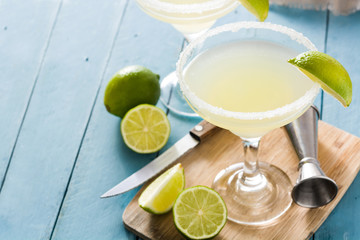 Margarita cocktails with lime in glass on blue wooden table