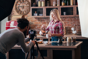 Homemade cooking. Baking hobby. Backstage photography. Woman with copper kettle and pastries. Man with camera.