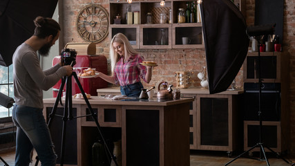 Homemade bakery. Cooking blog. Backstage photography. Man with camera shooting young woman with pastries.