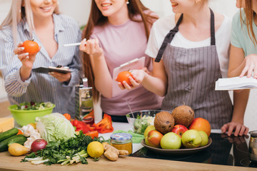 Culinary courses. Communication and food education. Women choosing organic vegetables and learning healthy diet recipes.