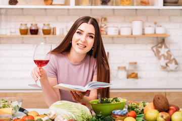 Evening at home. Cooking hobby. Smiling young woman with red wine glass. Book of healthy recipes in hands.