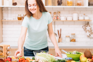 Healthy weight loss and nutritional balance. Woman lifestyle. Young female preparing salad. Organic foods assortment.