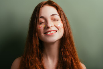 Glitter makeup. Perfect fresh skin. Woman youth beauty. Smiling young female. Eyes closed. Green background.