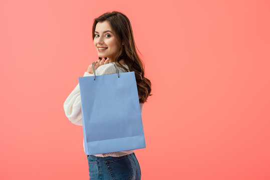 smiling and attractive young woman holding shopping bag isolated on pink