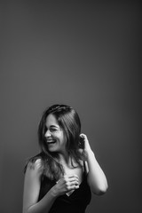 Young woman with toothy smile. Happiness and euphoria. Laughing with eyes closed. Black and white portrait. Copy space.