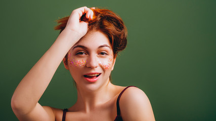 Cute young woman portrait. Redhead female messing hair. Fun and flirty mood. Copy space on green background.