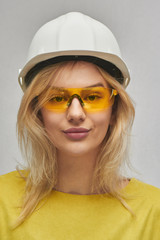 Portrait of young sexy blond woman engineer in construction helmet and glasses gently smiling at camera isolated on white background in studio