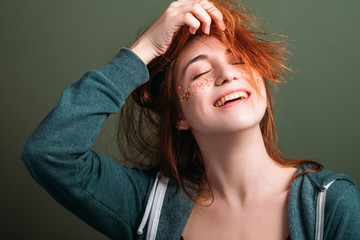 Cute young woman portrait. Fun and happiness. Redhead female messing hair. Toothy smile. Eyes closed.