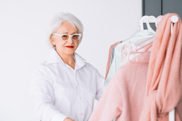 Senior fashion style. Shopping experience. Elderly lady looking at camera while choosing outfit.