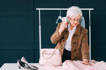 Senior elegant business female. Wardrobe shopping. Elderly lady choosing new outfit considering fashion trends.