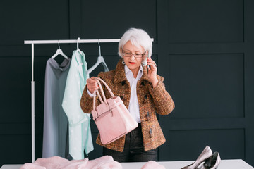 VIP shopping. Fashion showroom for senior business woman. Busy elderly lady choosing trendy outfit while talking on smartphone.