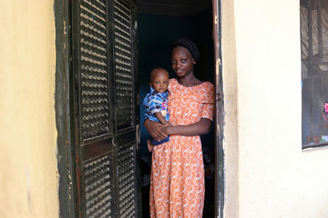 Noimot Shuaib Ajoke, 18-year-old first time voter, carries her child as she poses in Malete in Kwara State