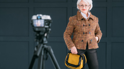 Successful senior woman. Fashion coach. Blogging lifestyle. Elderly lady posing for mobile video.