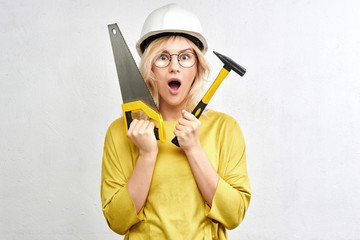 Surprised hot builder engineer with open mouth, tools, construction helmet, glasses, saw and hammer in white studio. Concept repair and service