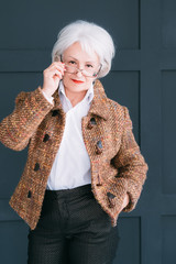 Stylish senior lady portrait. Lifestyle look. Confidence and elegance. Successful elderly woman posing in autumn outfit.
