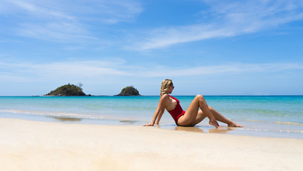 Beautiful Young Blonde Girl Relaxing in the shoreline and looking into the distance of the tropical Beach of Nacpan in El Nido, Palawan, Philippines