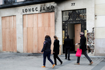 "People walk past a Longchamp shop damaged during the last ""yellow vests"" protest on the Champs Elysees avenue in Paris"