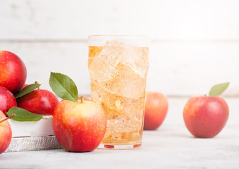 Glass of homemade organic apple cider with fresh apples in box on wooden background with sun light