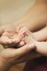 Fototapeta Stópki niemowlaka w dłoniach mamy obraz