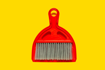 Red dustpan and brush lying on yellow background. In the style of pop art. Top view.