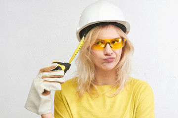 Beautiful blonde engineer in construction helmet, gloves and glasses thinks with pensive face on white background, horizontal shot with copy space