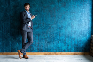 Full length portrait of young handsome businessman with smile pointing with finger.