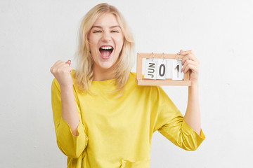 Happy woman in yellow clothes smiles, laughs and rejoices first of June on calendar on white background. Summer vacation, travel, holidays